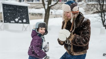 teen and child playing in snow
